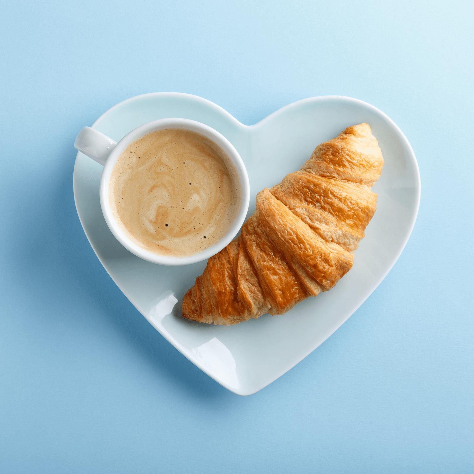 café croissant sur une assiette en forme de coeur